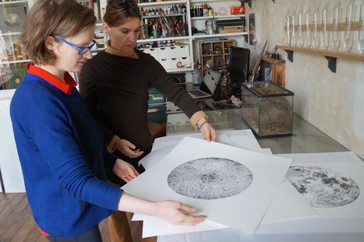 Anaïs Tondeur montre quelques reproductions de ses dessins de la Lune, à Marie Mirepois, dans son atelier de Montreuil.
